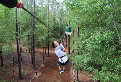A girl ziplines through the treetops at Orlando Tree Trek.
