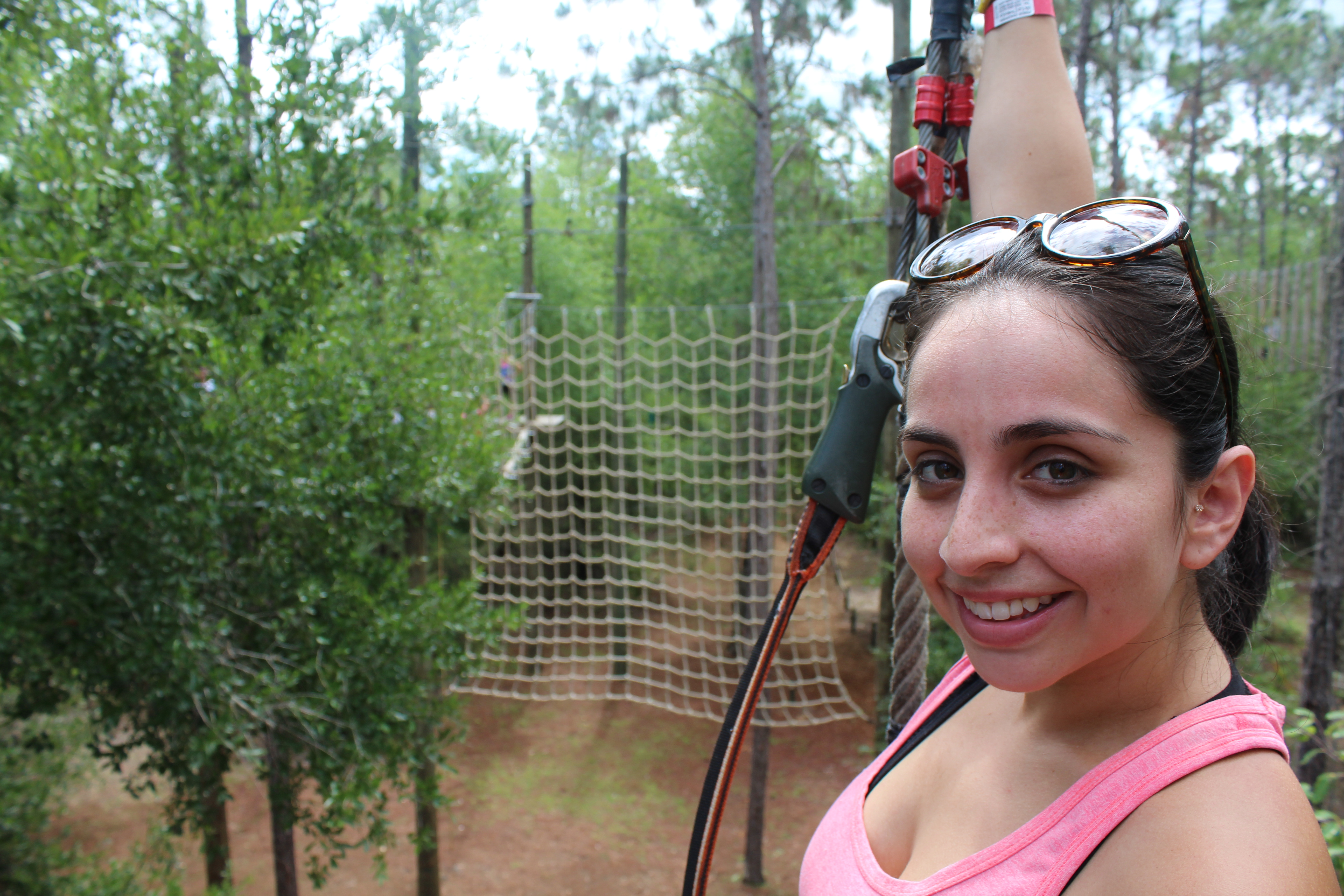Guest smiling while climbing the ropes course at Orlando Tree Trek.