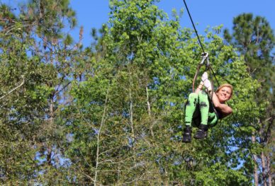 a guest ziplines through the treetops at Tree Trek.