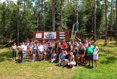 Travel agents in front of Orlando Tree Trek sign.