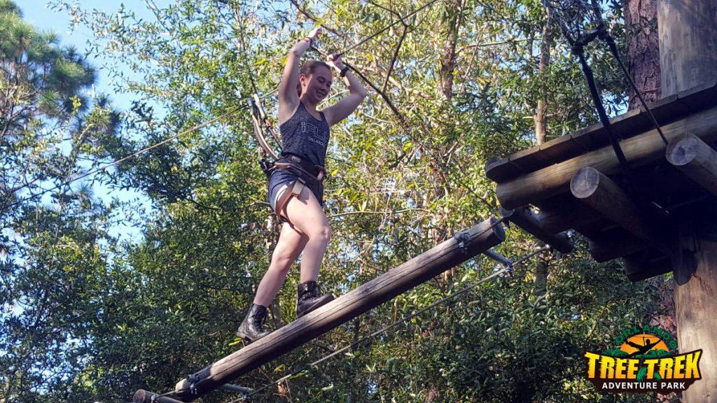 Girl walking on log obstacle at Orlando Tree Trek