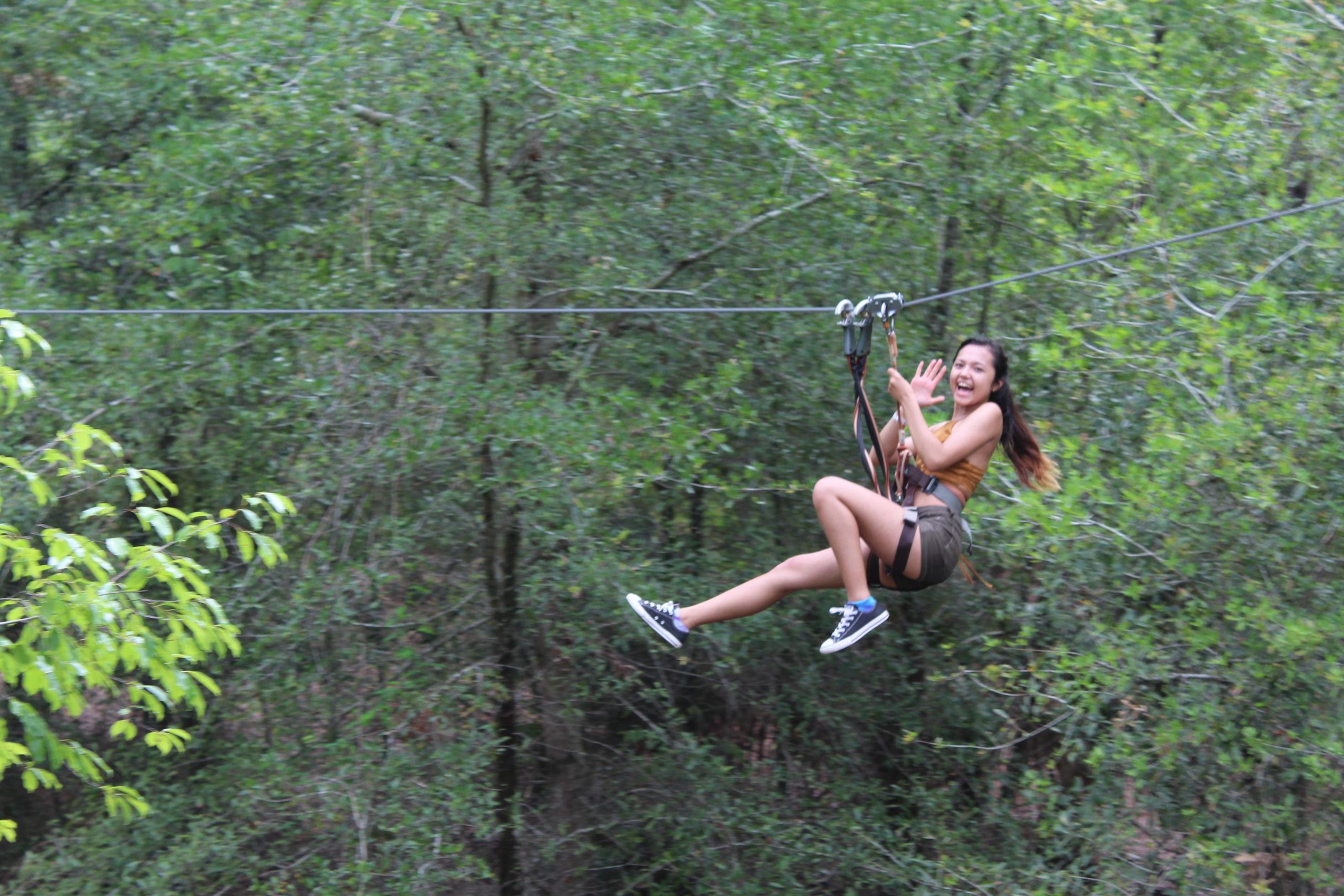 Woman ziplines through the trees at Orlando Tree Trek Adventure Park.